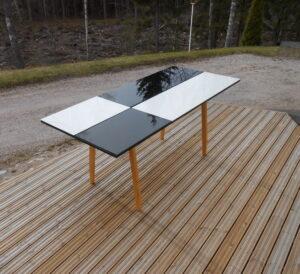 Design pöytä jossa on vaikutteita 1950-luvun suunnittelijoilta. Pöydän kansi on mäntyä, jalat koivua ja kannen pinnassa on reunahiottua karkaistua lasia. Pöytä on tilaustuote ja valmistamme niitä asiakkaiden toiveiden mukaan. Kuvien pöytien mitat ovat pituus 180 cm, leveys 81 cm ja korkeus 76 cm.